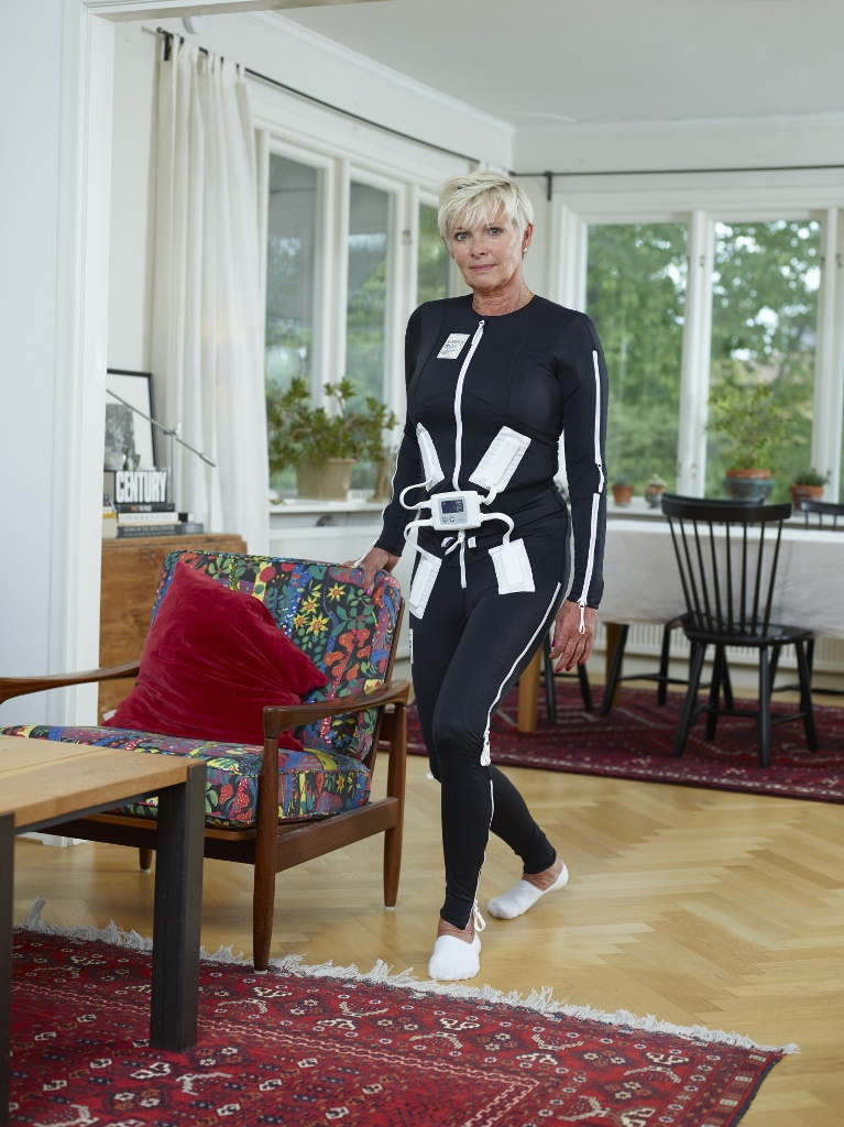 Woman wearing two piece track suit with electrodes attached.