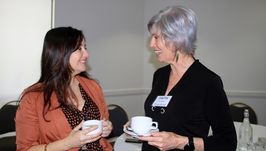 Two women enjoying a cup of tea and laughing.